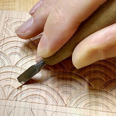 切込み入れた箇所と交わるように平刀で斜面を彫る(青海波)